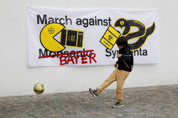 """A boy kicks a ball in front of a protest banner before the demonstration """"March against Bayer & Syngenta"""" in Basel"""