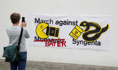 """A man takes a pictures of a protest banner before the demonstration """"March against Bayer & Syngenta"""" in Basel"""