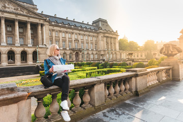 Young girl tourist sits on the background of the Royal Palace in Brussels and looks into the city map, Belgium