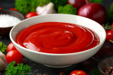 Homemade ketchup sauce in white bowl with vegetables and herbs