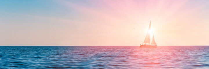 Banner 3:1. Sailboat in the sea in the evening sunlight over sky background. Luxury summer...