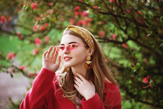 Outdoor close up portrait of young beautiful fashionable happy smiling girl with long blond hair, wearing trendy yellow headband, plastic pink color sunglasses, big earrings, posing in blooming park