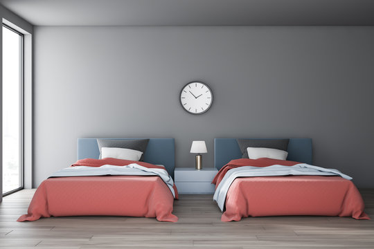Gray bedroom interior with two beds and clock
