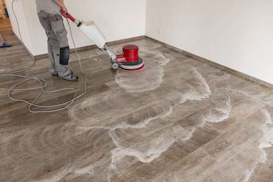 Man cleans the tile floor with a machine in an apartment.