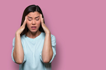 Woman overwhelmed with stress and concern, confusion and doubt, hands to head, on pink background copy space