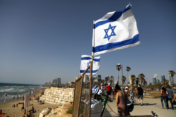 Israeli flags are seen on the beach as people walk by on the eve of the 2019 Eurovision song contest final in Tel Aviv, Israel