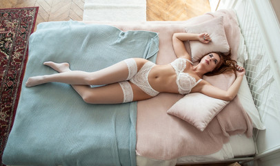 girl with red hair in white lingerie and stockings lies thoughtfully on the bed. View from above.