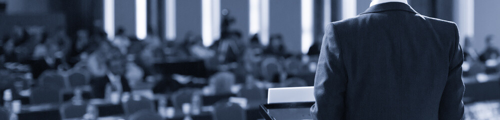 Speaker at Conference Stage. Executive Business Entrepreneur at Seminar Photo. Business Presentation Presenter Speech at Meeting. Corporate Forum Event for Investor Audience. Black and White