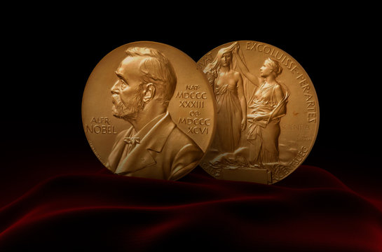 Alfred Nobel Prize. Two medals standing on red fabric.
