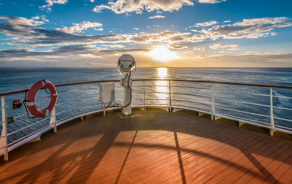 Wooden deck and railing from cruise ship. Beautiful sunset and ocean view.
