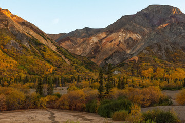 Fall colors mix yellow with the evergreen of a mixed forest covering the gravel slopes of small mountains