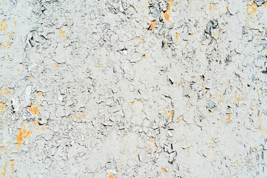 Yellow and gray cracked paint on a metal surface.