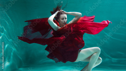 ba81032dc9 Mystical underwater portrait of a beautiful young woman in a red dress. Girl  swimming underwater