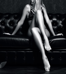 Sexy young blonde lady in black lingerie on dark brown leather sofa