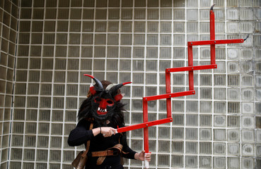 """A member of the """"Los Diablos de Sarracin de Aliste"""" folk group poses for a photo before the parade of the 14th International Festival of the Iberian Mask in Lisbon"""