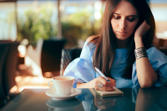 Woman Writing Down Ideas on Paper in a Coffee Shop