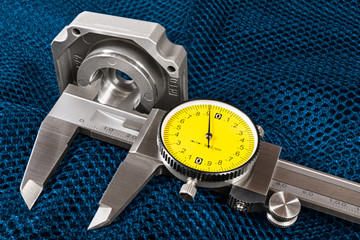 Caliper jaws closeup. Internal hole diameter measuring on a blue net background. Measurement of aluminum cast of bearing housing. Precise metal tool. Round yellow dial. Copy space. Quality inspection.