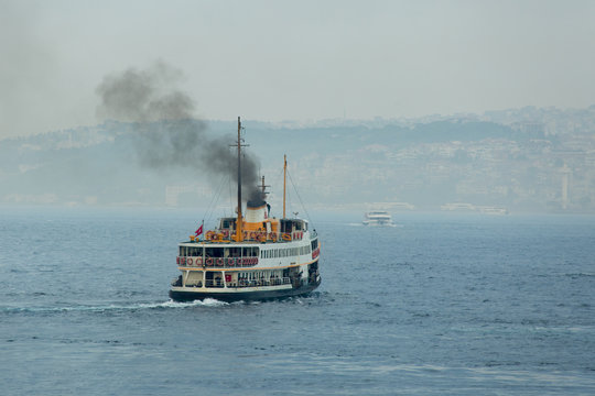 Ferry boat sails on foggy weather and smoke coming from its chimney. Istanbul, Turkey