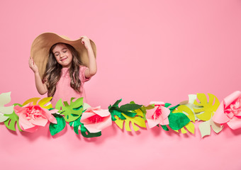 Portrait of a little girl in a summer hat on a pink background
