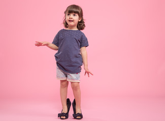 Funny little girl is a fashionista in the shoes of the mother