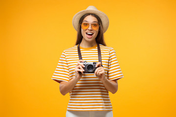 Positive European tourist girl with retro camera isolated on yellow background excited with shot she is going to take