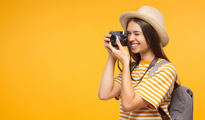 Good-looking Caucasian girl taking pictures with retro camera on vacation isolated on yellow background, copyspace on left