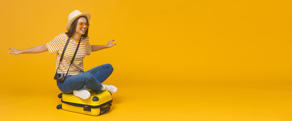European Caucasian woman sitting on suitcase and spreading arms as if she is flying, concept of travelling, isolated