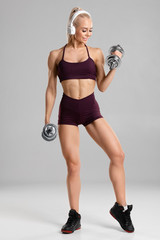 Fitness woman doing exercise for biceps on gray background. Happy woman workout with dumbbells, isolated