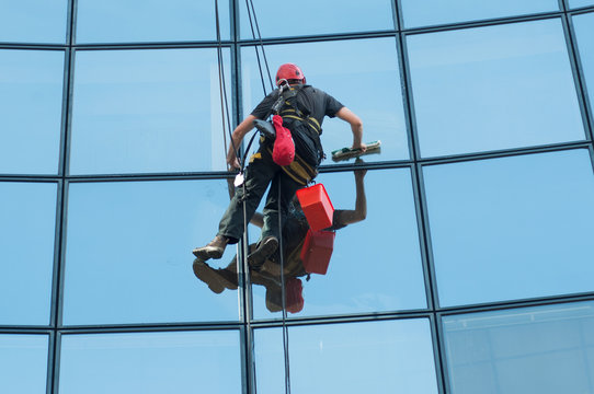 portrait of worker washing windows of the modern building.