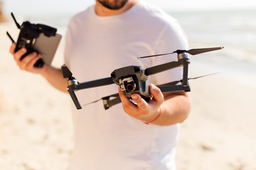 Young man holding drone before flight near ocean or sea. Pretty guy prepare to pilot outdoor
