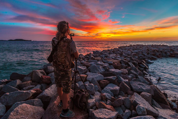 Travel photographer with tripod on breakwater rocks at Anse Kerlan, Seychelles with scenic colorful sky. Kerlan Beach, southwest Praslin is famous for spectacular sunsets on Cousine and Cousin islands