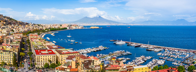 Naples city and port with Mount Vesuvius on the horizon seen from the hills of Posilipo. Seaside landscape of the city harbor and golf on the Tyrrhenian Sea