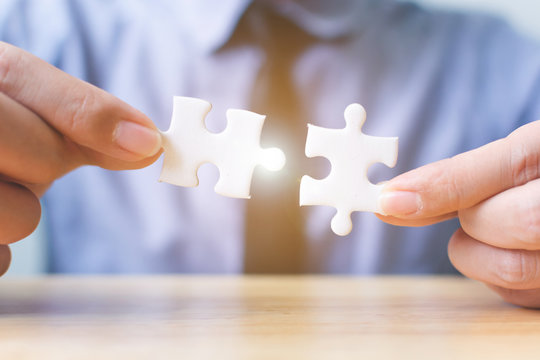Strategic management and business solutions for success, Hand of businessman connecting jigsaw puzzle