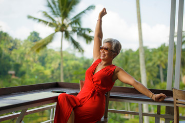 attractive and happy Asian Indonesian middle aged woman with grey hair relaxed chilling cheerful and carefree and tropical holidays resort enjoying Summer getaway