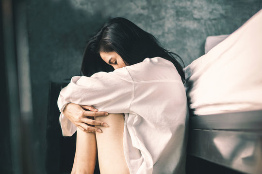 depress Asian woman sitting in bedroom feeling lonely and sad