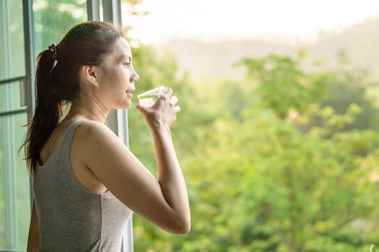 Asian woman drinking clean water in the morning next to the window with nature background