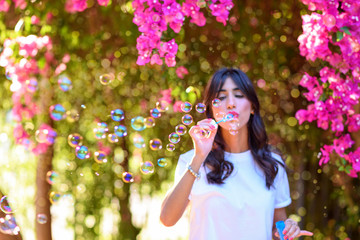 Returning to nature to connect with the inner self. Happy beautiful young woman blowing soap bubbles outdoor.