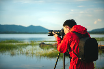 Travel photographer taking a photo with nature the lake in sunset with camera on tripod, Focusing attention nature mountain view and lake,  Natural photography relaxing concept.