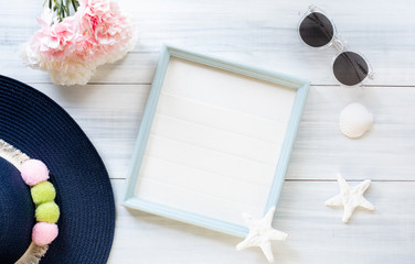 Wall Mural - top view of summer blue female hat and picture frame with sunglasses and seashell and star fish decoration on white wood table.summer vacation