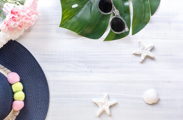 Wall Mural - top view of summer blue female hat with sunglasses and shell and star fish decoration on white wood table.summer vacation