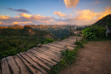 Young Asian woman take pictures in the sunset view point of Ban Ja-Bo, Pang Ma Pha, Mae Hong Son, Thailand