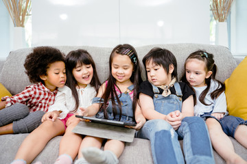 group of little children watching film movie cartoon together on digital tablet. Kids playing with tablet with friends at home
