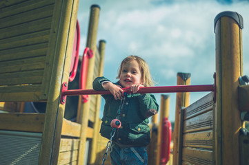 Little toddler on play equipment in the playground