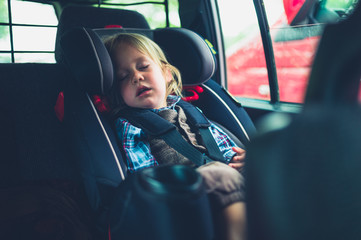 Little toddler sleeping in a car seat