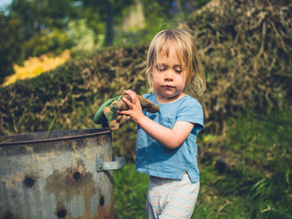 Little toddler putting weeds in an incinerator