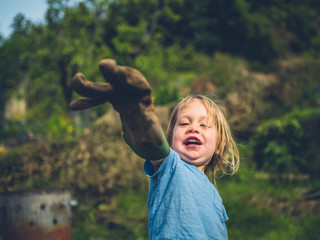 Little toddler posing with garden glove
