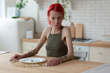 Anorexic woman having awful look sitting in the kitchen