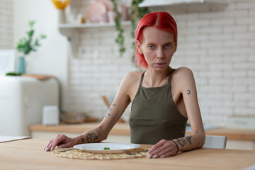 Red-haired anorexic woman sitting in the kitchen alone