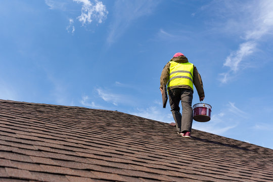 Workman standing on tile roof of new home under construction