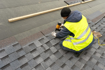 Workman using pneumatic nail gun install tile on roof of new house under construction Fototapete
